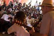 A crowd watches as Canadian artist Dave Bidini plays a song during a performance by the Liberian Dance Troupe (LDT) at the Buduburam refugee settlement, roughly 20 km west of Accra, Ghana's capital, on Saturday April 14, 2007. One of the main goals of the LDT is to teach young refugee children, many of which have never seen Liberia, about their country's music, dance and culture. The Buduburam refugee settlement is still home over 30,000 Liberians, most of which have mixed feelings about returning to Liberia.