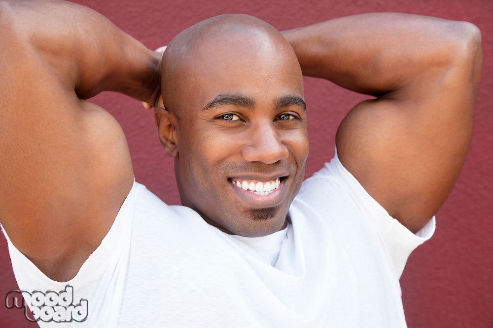 Portrait of a young physically fit African American man with hands behind head