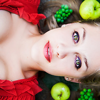 Portrait of blond girl, surrounded by green fruits