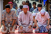 "08 AUGUST 2013 - BANGKOK, THAILAND: Men pray outside during Eid al-Fitr services at Haroon Mosque in Bangkok. Eid al-Fitr is the ""festival of breaking of the fast,"" it's also called the Lesser Eid. It's an important religious holiday celebrated by Muslims worldwide that marks the end of Ramadan, the Islamic holy month of fasting. The religious Eid is a single day and Muslims are not permitted to fast that day. The holiday celebrates the conclusion of the 29 or 30 days of dawn-to-sunset fasting during the entire month of Ramadan. This is a day when Muslims around the world show a common goal of unity. The date for the start of any lunar Hijri month varies based on the observation of new moon by local religious authorities, so the exact day of celebration varies by locality.      PHOTO BY JACK KURTZ"