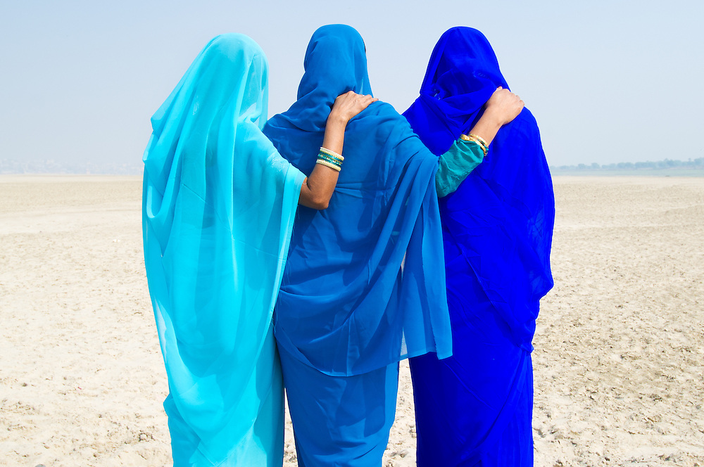Three women wearing different shades of blue sari's (saree) wallking on the banks of river Ganga, Varanasi (India)