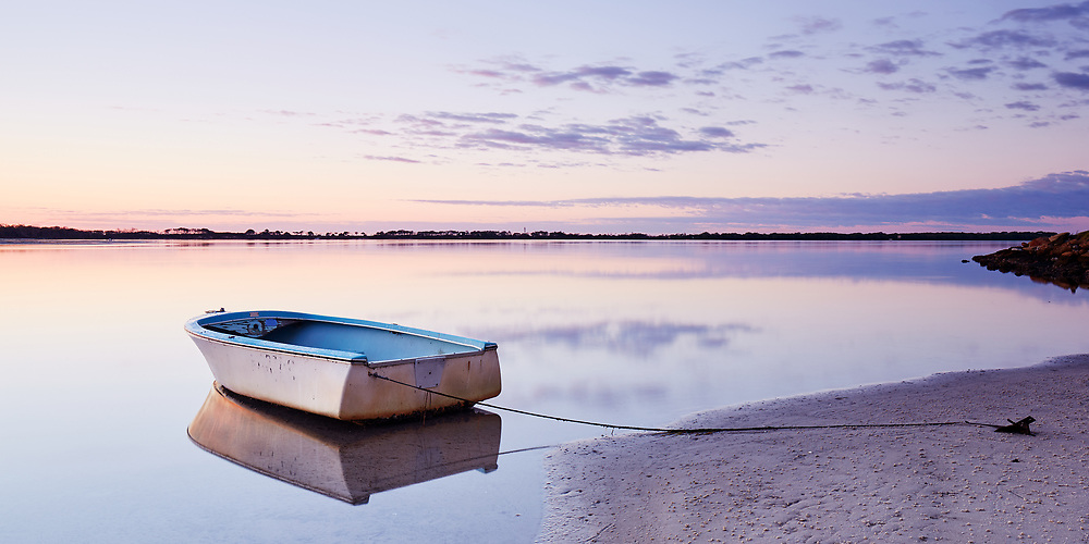 A lone dingy rests in the calm waters of Golden Beach at dawn.