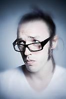 studio shot portrait of young expressive man making faces