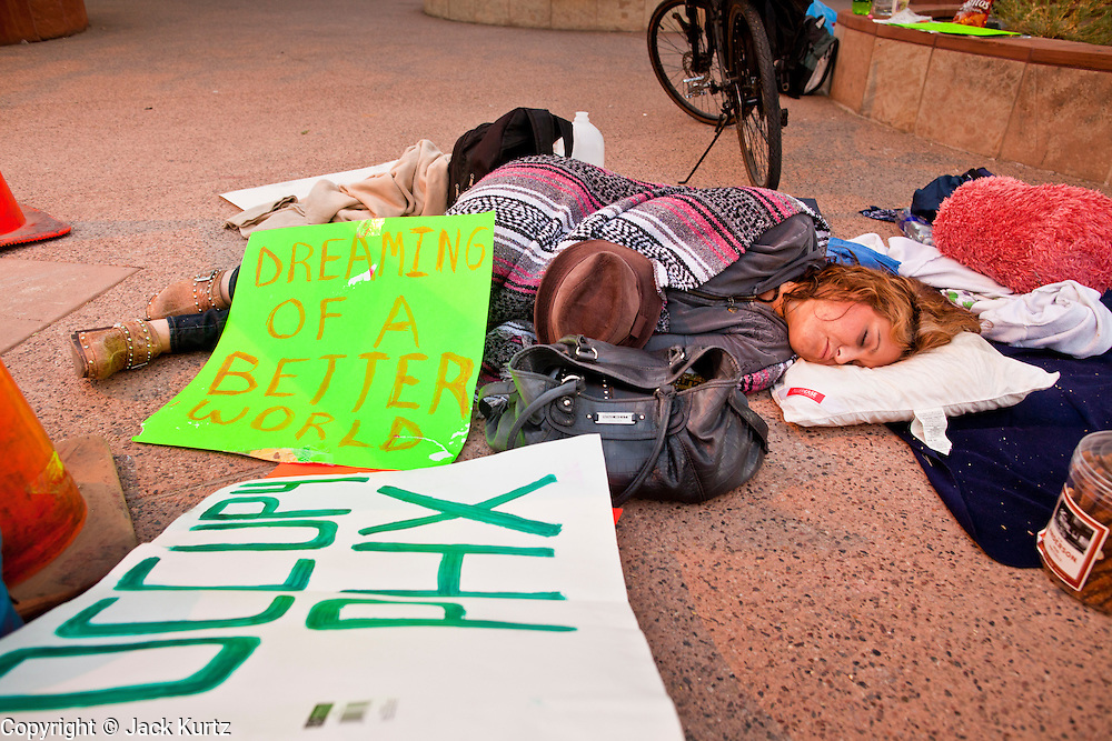 17 OCTOBER 2011 - PHOENIX, AZ:   A woman sleeps on the sidewalk during the Occupy Phoenix protest in Phoenix, Monday morning. About 40 people spent Sunday night on the sidewalks around the Cesar Chavez Plaza in Phoenix, AZ, the defacto headquarters of the Occupy Phoenix protest. Early Monday morning they got up to continue their chants and protests against Wall Street, the growing income gap between rich and poor in the US, and money in politics. Monday marks the third day of Occupy Phoenix.    PHOTO BY JACK KURTZ