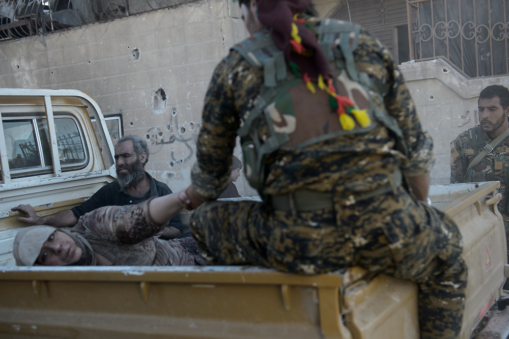 A woman lies on the back of a pick-up truck in the eastern part of Raqqa. She was evacuated by the Syrian Democratic Forces (SDF) from a neighborhood where the fighting between SDF and ISIS was still going on. Raqqa, Syria, October 12, 2017
