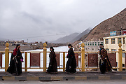 Women walk across a bridge that spans the Mekong river in the town of Zado, Tibet (Qinghai, China).