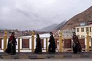 Women walk across a bridge that spans the Mekong river in the town of Zado, Tibet (Qinghai, China).