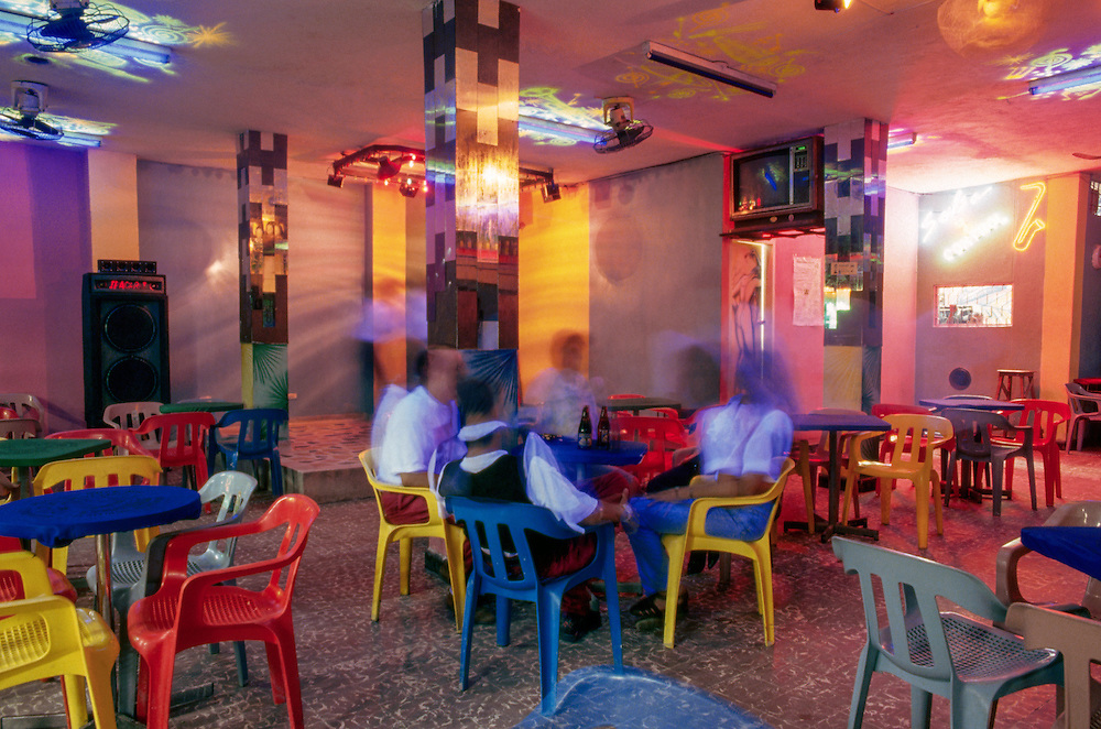 ca. 1980-1995, Barranquilla, Colombia --- People drink beer in the technicolor interior of the Salsa discotheque, Barranquilla, Colombia. --- Image by © Jeremy Horner/Corbis