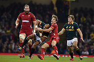Liam Williams of Wales tackles South Africa's Cornal Hendricks. Dove Men series 2014, autumn international rugby match, Wales v South Africa at the Millennium stadium in Cardiff, South Wales on Saturday 29th November 2014<br /> pic by Andrew Orchard, Andrew Orchard sports photography.
