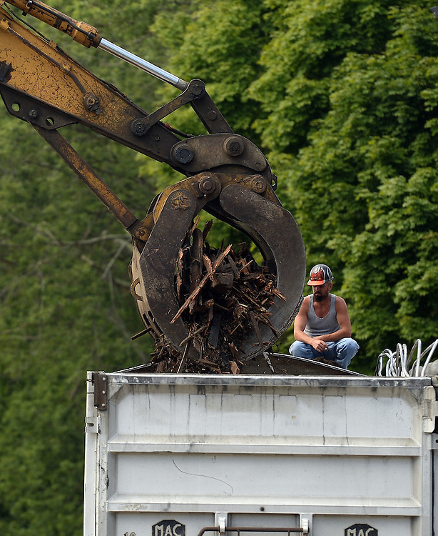 7/25/16 :: REGION :: STAND ALONE :: A worker watches as a claw excavator fills a truck with debris as crews from Stamford Wrecking tear-down St. Michael The Archangel Roman Catholic Church on Liberty St. in Pawcatuck Monday, July 25, 2016. The church has been closed since April of 2012 when structural problems were found. The new church will be built on the original foundation. (Sean D. Elliot/The Day)