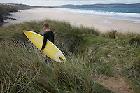 Man carrying surfboard down hill torwards sea back view