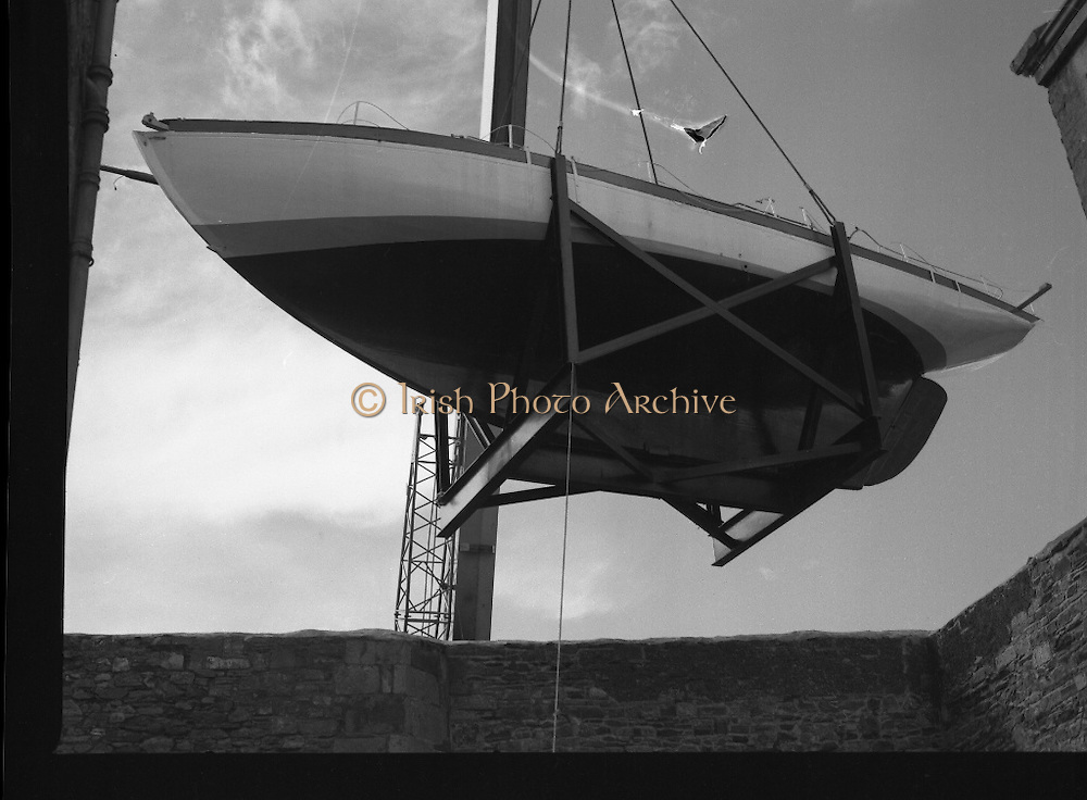 """The """"Asgard """" at Kilmainham Jail..1979..01.04.1979..04.01.1979..1st April 1979..The historic yacht """"Asgard"""" owned by Erskine Childers was brought to Kilmainham Jail,Dublin. The vessel had to be hoisted ,by crane,over the outer wall of the jail. It was placed as part of a future exhibition to be set up by The National Museum..Image shows the yacht clearing the top of the jail wall."""
