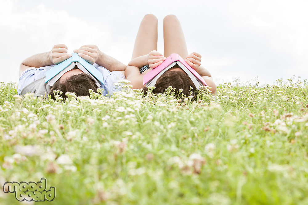 Relaxed young couple covering faces with books while lying on grass