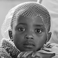 Photo Randy Vanderveen<br /> Musanze District, Rwanda<br /> 2015-05-23<br /> A young girl with an onion sack hat, The youngster was attending a Children of Hope (a support group for children affected by HIV/AIDS through infection or having a parent or sibling infected with the virus.