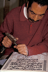 Africa, Morocco, Fes, Fes el-Bali medina, man chisels Arabic script onto stone tablet MR