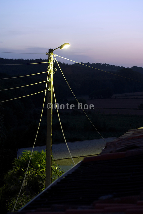 street light at dusk with hilly landscape in the background