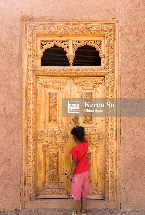 Uighur chidl with wood door, Turpan, Xinjiang, China