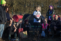Harefield, UK. 19 January, 2020. Activists from Extinction Rebellion and Stop HS2 hold an assembly during a 'Stand for the Trees' event timed to coincide with tree felling work for the high-speed rail link on land from which bailiffs acting for HS2 had evicted activists living in the Colne Valley wildlife protection camp almost two weeks previously. The trees behind them are expected to be felled imminently for HS2; 108 ancient woodlands will be destroyed by the high-speed rail link.