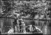 Men unloading sand taken from a river bed. The sand is used in the building industry. Near Kalutara. Probably Kalu Ganga<br />