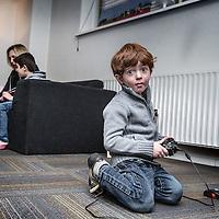 Nederland, Amsterdam, 18 februari 2016.<br />Aan de Mauritskade nummer 17 zit sinds kort een kleinschalige opvang voor Syrische vluchtelingen. Initiatiefneemster is Lian Primus.<br />Op de foto: Mohamed en Yazan de kinderen van Ammar en Iman worden vermaakt met boeken lezen en computerspelletjes.<br /><br /><br /><br />Foto: Jean-Pierre Jans