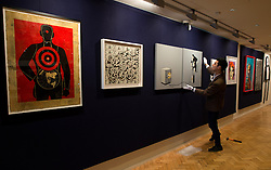 © Licensed to London News Pictures. 12/04/2013. London, UK. Gallery assistant hangs  Banksy's Monkey Detonator during the preview for Climbing The Walls With Banksy at Bonham's Urban Art Sale at Bonham's auction house in London, April 12, 2013. Photo credit : Peter Kollanyi/LNP