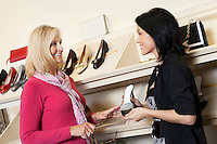 Happy mature salesperson with mid adult customer in shoe store