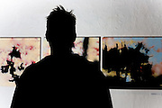 Ryan's silhouette in front of three of his paintings.