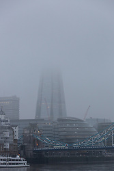 © Licensed to London News Pictures. 18/12/2016. LONDON, UK.  The London Shard is seen shrouded in fog this morning. Foggy weather continues to disrupt flights from London airports this morning.  Photo credit: Vickie Flores/LNP