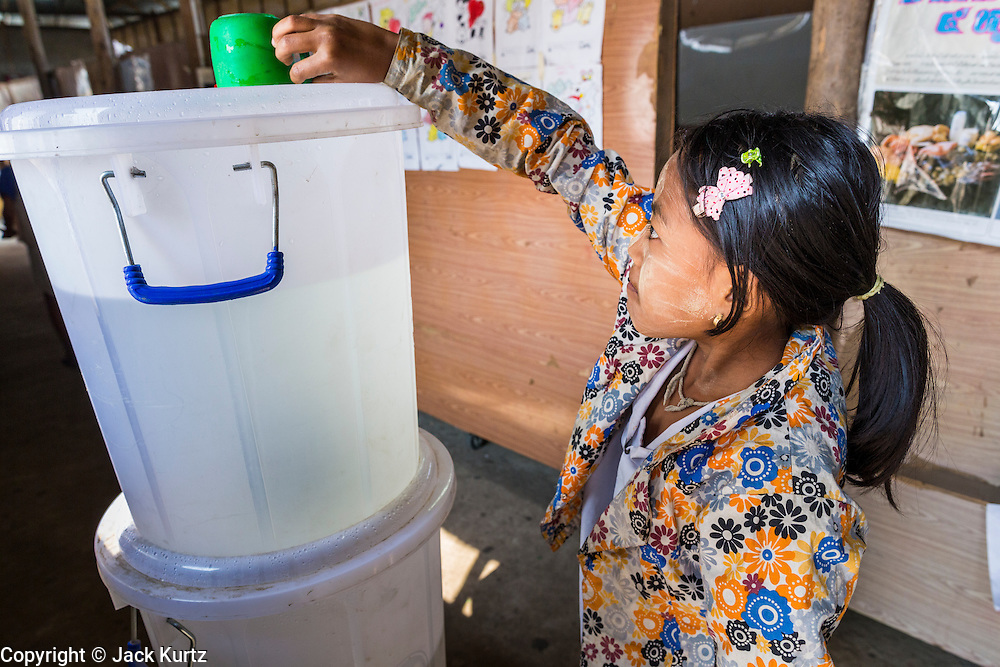04 MARCH 2014 - MAE SOT, TAK, THAILAND: A girl puts the communal water cup on top of the water tank in the hallway at the Sky Blue School. There are approximately 140 students in the Sky Blue School, north of Mae Sot. The school is next to the main landfill for Mae Sot and serves the children of the people who work in the landfill. The school relies on grants and donations from Non Governmental Organizations (NGOs). Reforms in Myanmar have alllowed NGOs to operate in Myanmar, as a result many NGOs are shifting resources to operations in Myanmar, leaving Burmese migrants and refugees in Thailand vulnerable. The Sky Blue School was not able to pay its teachers for three months during the current school year because money promised by a NGO wasn't delivered when the NGO started to support schools in Burma. The school got an emergency grant from the Burma Migrant Teachers' Association and has since been able to pay the teachers.    PHOTO BY JACK KURTZ