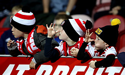 Young Brentford fans playfully tease the Birmingham City substitutes as they warm up in front of them