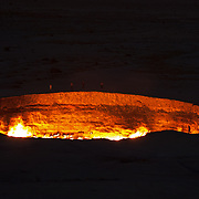 People walk around Darvaza gas crater in early evening, as the burning natural gas glows in the darkness