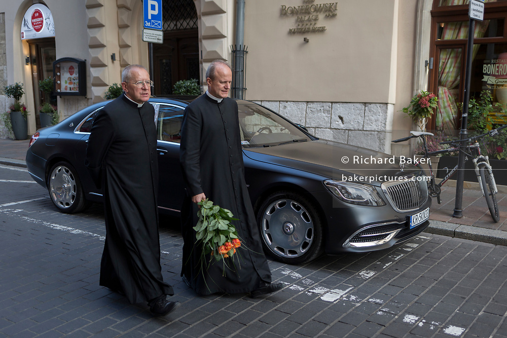 A priest walks past a luxury Mercedes car with a church colleague, holding a bunch of red flowers on a central Krakow street, on 24th September 2019, in Krakow, Malopolska, Poland.