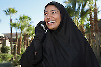 Muslim woman in black hijab talking on mobile, laughing