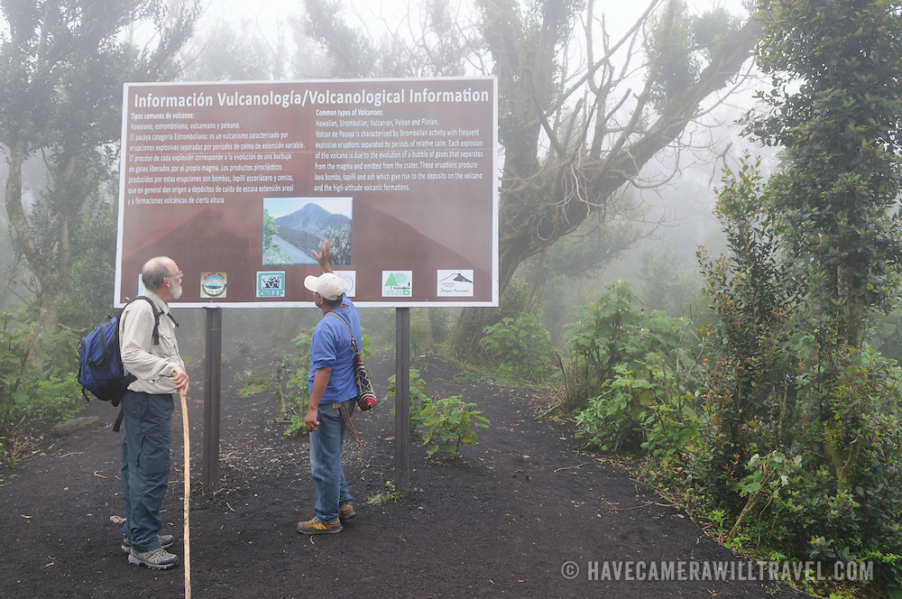 One of the local tour guides provides information to a hiker near the summit of Pacaya Volcano on a misty morning. Pacaya is an active volcano that forms part of the Central America Volcanic Arc. It forms a popular tourist destination easily accessible from Antigua and Guatemala City. Situated within the Pacaya National Park, it rises to 2,552 metres (8,373 ft). Its last major eruption, which caused considerable damange to nearby villages and reshaped the summit, was in May 2010. That eruption and scattered volcanic ash over much of the nearby area, prompting school closings and emergency evacuations and cleared much of the vegetation near the top of the mountain.