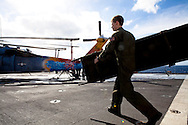 A member of HSC 28, a helicopter sea combat detachment out of Norfolk, Virginia, carries a stretcher on the flight deck of the USNS Comfort, a naval hospital ship, as the ship makes its way to help survivors of the earthquake in Haiti on Monday, January 18, 2010 in the Atlantic Ocean off the coast of the United States.