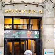 NLD/Amsterdam/20160121 - Winkels in het Amsterdamse straatbeeld, gebouw van Beursplein 5 Amsterdam met de koersen van Heineken, ING en Philips op de gevel