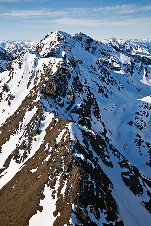 Longer days and warmer temperatures in spring begin to expose the ridgelines of the snow covered Chugach Mountains in Chugach State Park near Anchorage in Southcentral Alaska. Morning.