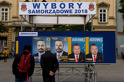 October 4, 2018 - Krakow, Poland - Polish citizens are seen as they look to a board with information about the local elections at the Main Square. On October 21, 2018 Polish citizens will vote for thousands of councillors and local mayors in regional, county and parish elections. (Credit Image: © Omar Marques/SOPA Images via ZUMA Wire)