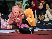 17 JULY 2015 - BANGKOK, THAILAND:     A woman talks to her daughter during Eid al-Fitr services at Ton Son Mosque in Bangkok. Eid al-Fitr is also called Feast of Breaking the Fast, the Sugar Feast, Bayram (Bajram), the Sweet Festival or Hari Raya Puasa and the Lesser Eid. It is an important Muslim religious holiday that marks the end of Ramadan, the Islamic holy month of fasting. Muslims are not allowed to fast on Eid. The holiday celebrates the conclusion of the 29 or 30 days of dawn-to-sunset fasting Muslims do during the month of Ramadan. Islam is the second largest religion in Thailand. Government sources say about 5% of Thais are Muslim, many in the Muslim community say the number is closer to 10%.          PHOTO BY JACK KURTZ