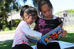 "Six-year old Cloy Rosas, right, reads with a friend after ""checking out"" a Sesame Street book on opening day of Salinas' first Little Library at El Gabilan Park in Salinas. Two more Little Libraries were installed on Wednesday, in Central Park and McKinnon Park, with two more slated to start this summer."