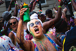 A woman is drenched in paint as day one, Children's Day, of the Notting Hill Carnival gets underway in London. London, August 25 2019.