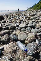 A single use clear plastic water bottle discarded on a rocky shoreline.