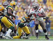 "GREEN BAY, WI - SEPTEMBER 25:  Rookie running back Carnell ""Cadillac"" Williams #24 of the Tampa Bay Buccaneers runs for some of his 158 yards while chased by linebacker Nick Barnett #56 of the Green Bay Packers at Lambeau Field on September 25, 2005 in Green Bay, Wisconsin. The Buccaneers defeated the Packers 17-16. ©Paul Anthony Spinelli *** Local Caption *** Carnell Williams;Nick Barnett"