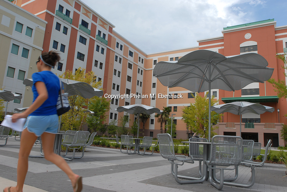 A student walks to class past a new dormitory at the University of Central Florida in Orlando, Florida.