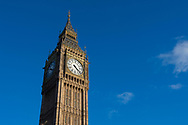 Low angle view of Big Ben, officially known as the Elizabeth Tower, against a blue sky in London, England.
