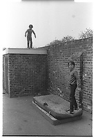 Kids jumping of a garage roof onto a pile of mattresses, South-East London, London street photography in 1982. Tri-X