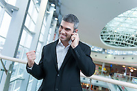 Businessman celebrates talking on mobile phone