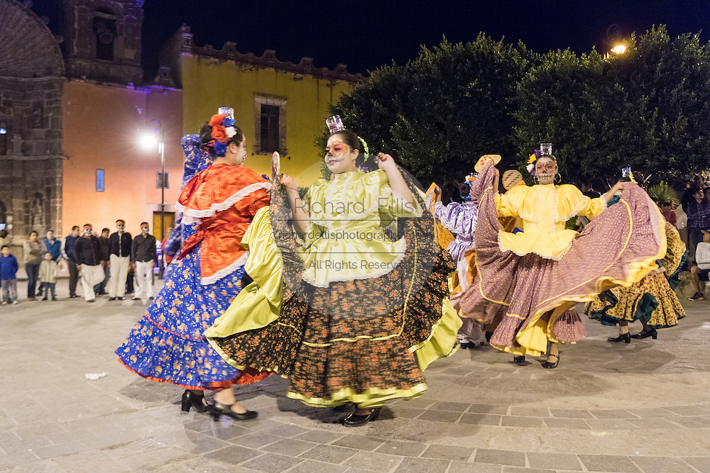 Young women dressed as La Calavera Catrina perform a folk dance during the Day of the Dead festival in the Plaza Civica October 28, 2016 in San Miguel de Allende, Guanajuato, Mexico. The week-long celebration is a time when Mexicans welcome the dead back to earth for a visit and celebrate life.