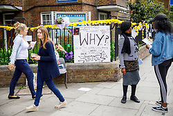 © Licensed to London News Pictures. 01/07/2017. London, UK. People lay flowers for the victims of the Grenfell Tower fire on Saturday, 1 July 2017 on Latimore Road in west London. Photo credit: Tolga Akmen/LNP