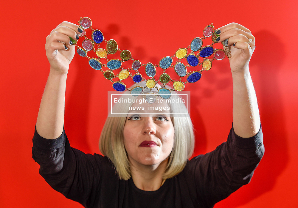 Courtney Lawler from the Incorporation of Goldsmiths examines a necklace from the MADE London collective which is made out of recycled glass and brass and is taking centre stage at the festival.<br /> <br /> © Dave Johnston/ EEm